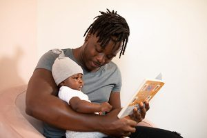 Photo: Man Reading to Baby