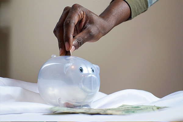 Photo: Hand putting money into Piggy Bank